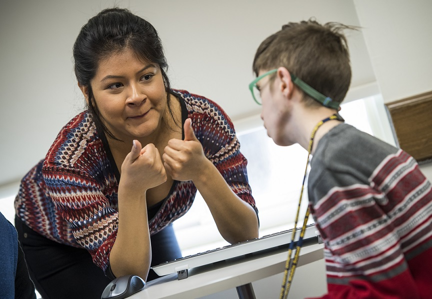 TWU students gives thumbs up to child in speech-language hearing lab.