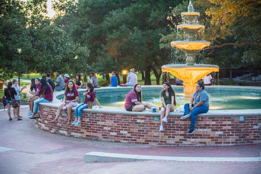 Students gathered at the TWU fountain at twilight.