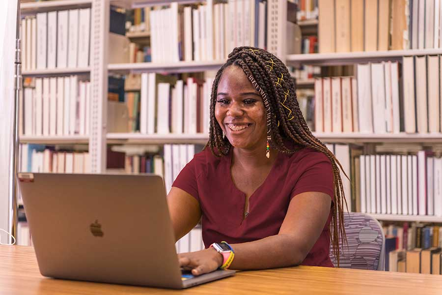 TWU student, Jada Sneed, works on a laptop alone in TWU's Denton campus library.