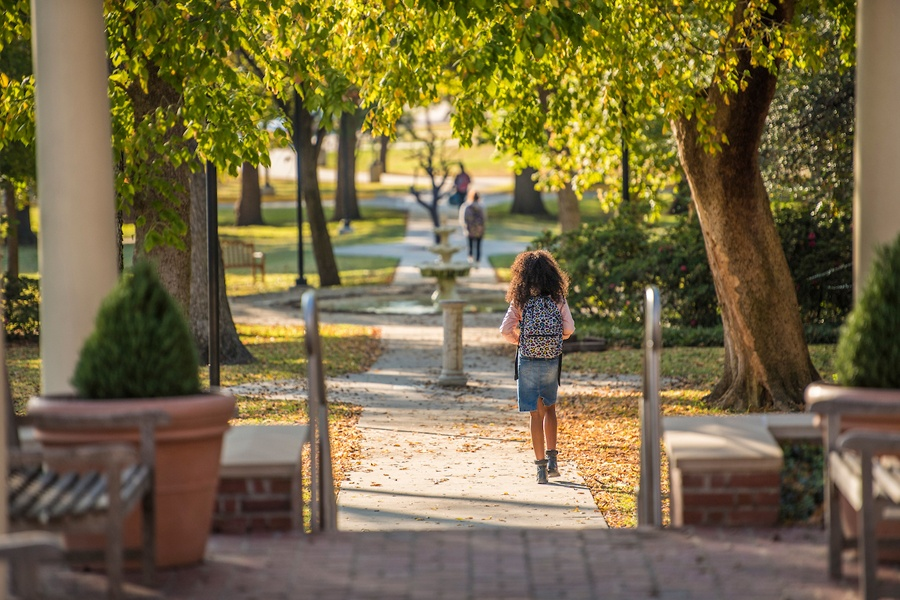 A TWU student walks through fall foliage near the Gertrude Lathrop Arbor.