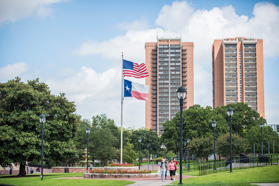 The American and Texas flags fly in front of the dorms on TWU's Denton campus