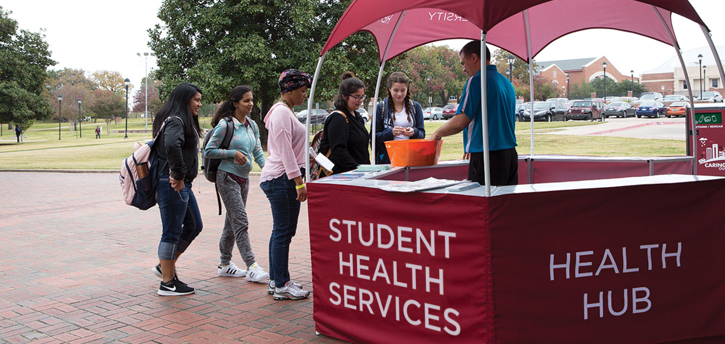 A group of students gather at an outdoor kiosk for free health supplies