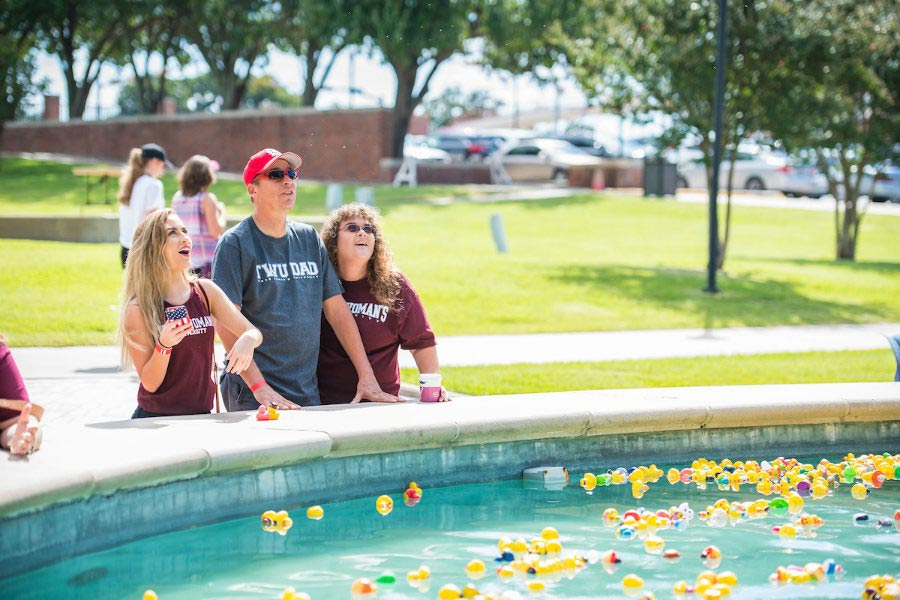 Family weekend, parents and daughter by fountain