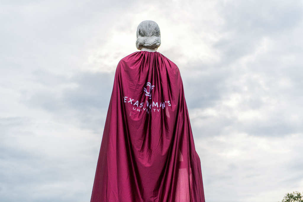 Statue of the Pioneer Woman wearing a cape with TWU's logo on it.