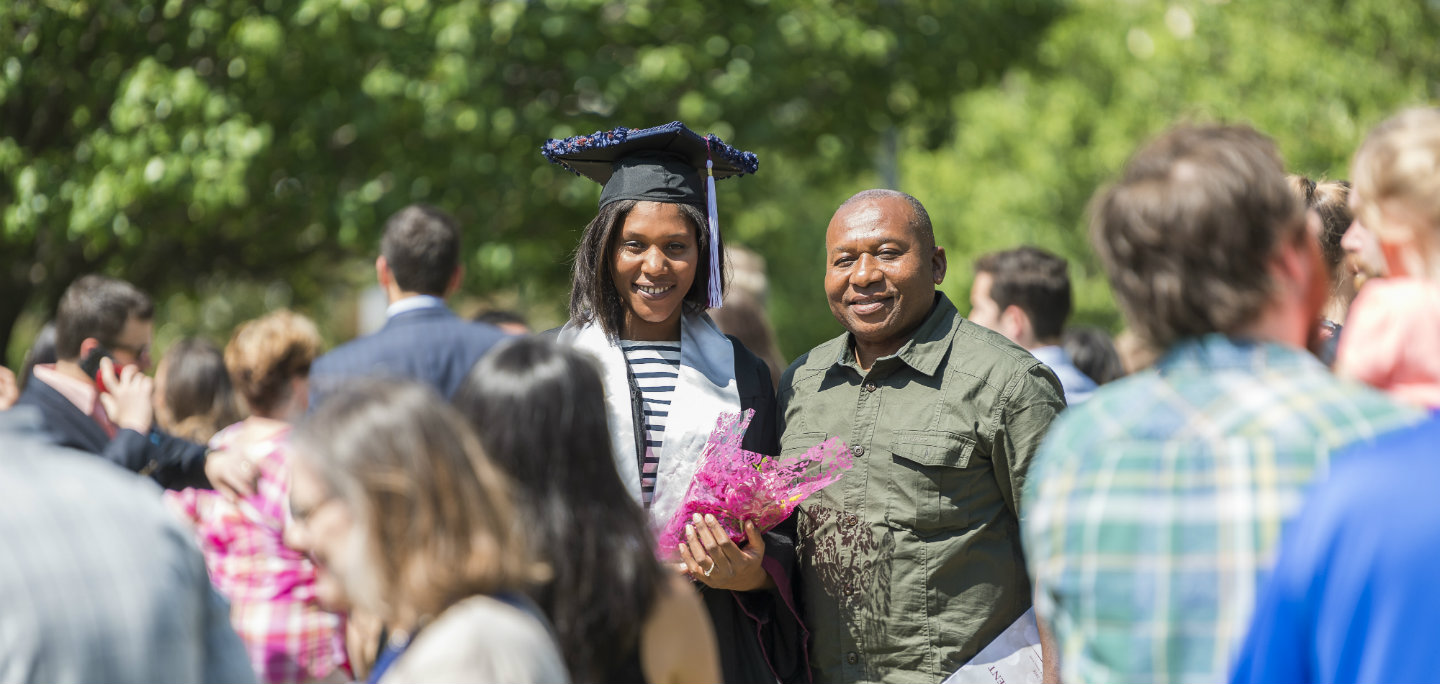 A TWU graduate stands out in the crowd in a cap and gown with her father by her side on TWU's Denton campus.