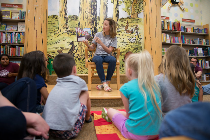 TWU student reads book to children.