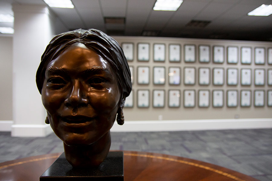 Statue sitting on a table with plaques in the background in the Texas Women's Hall of Fame in the Blagg-Huey Library.