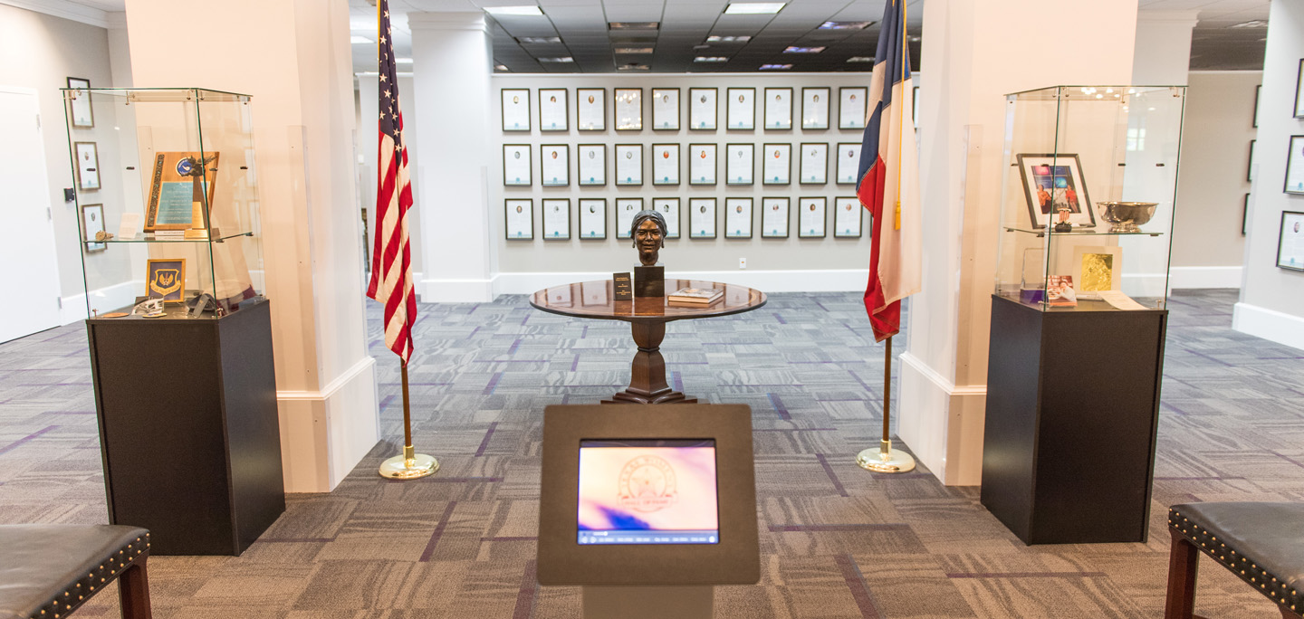 The Texas Women's Hall of Fame, with a statue sitting on a table with flags on either side. Plaques line the wall in the background.