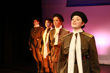 Four female students in WWII pilot outfits perform the play The Night Witches