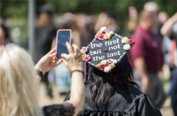 Student with decorated mortar board graduation cap stating 'the first...but not the last'.