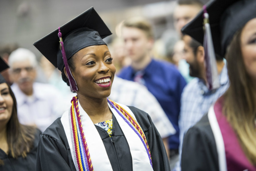 A TWU graduate in her graduation gown at commencement ceremony.