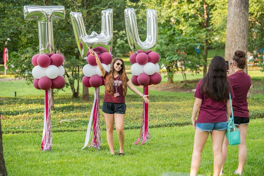 A TWU student poses in front of large balloons in the shape of TWU letters.