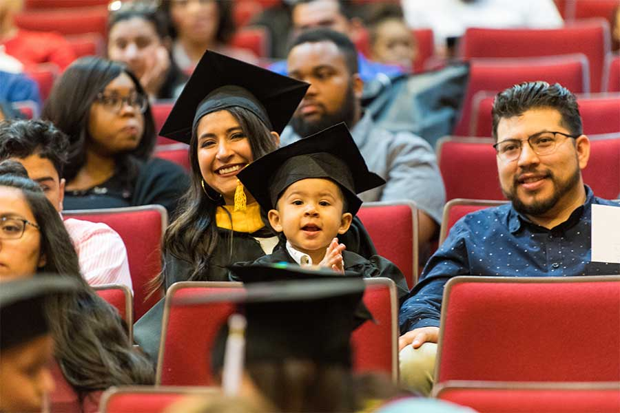 A child sits on the lap of a TWU student dressed in academic regalia in a crowd.