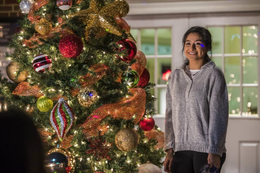 A TWU student posing next to a tree decorated with ornaments, lights, and ribbons.