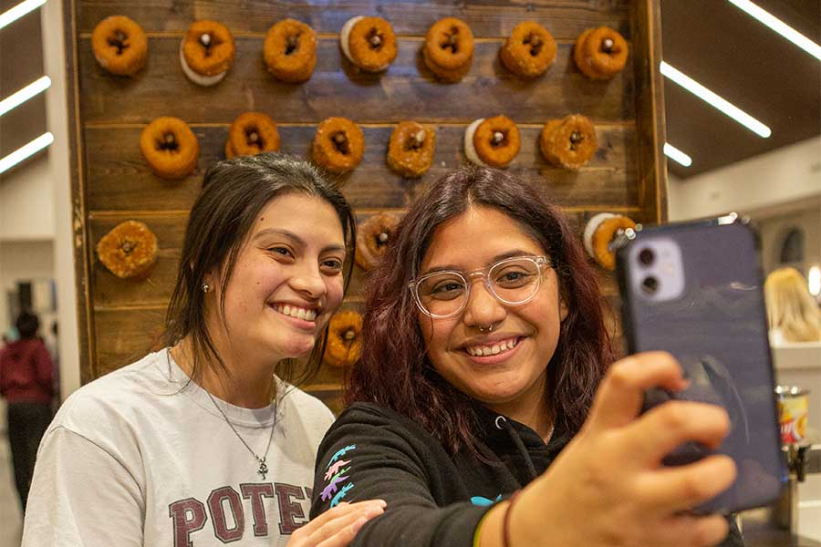 TWU students take a selfie in front of a donut wall in the Denton campus dining hall.