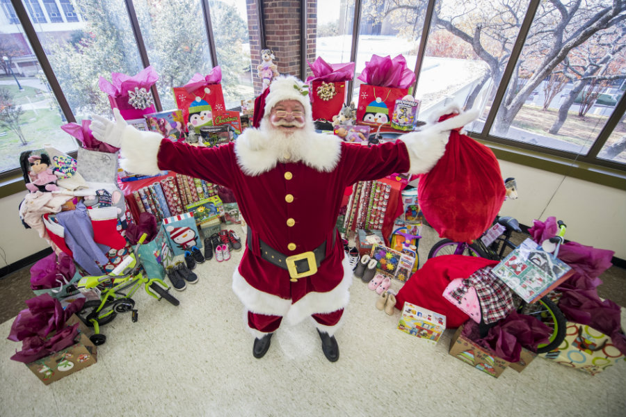 Santa standing with his arms out in front of a pile of toys and presents on TWU's Denton campus.