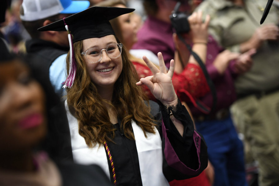 A graduate at her commencement ceremony holding up the TWU hand sign.