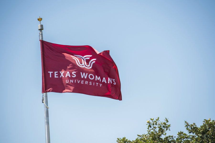 A maroon flag flying on TWU's Denton campus with the logo in white.