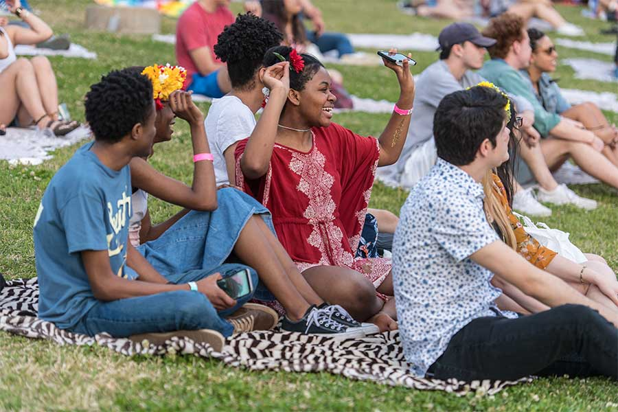 TWU students relax and listen to music on the lawn of the Denton campus.