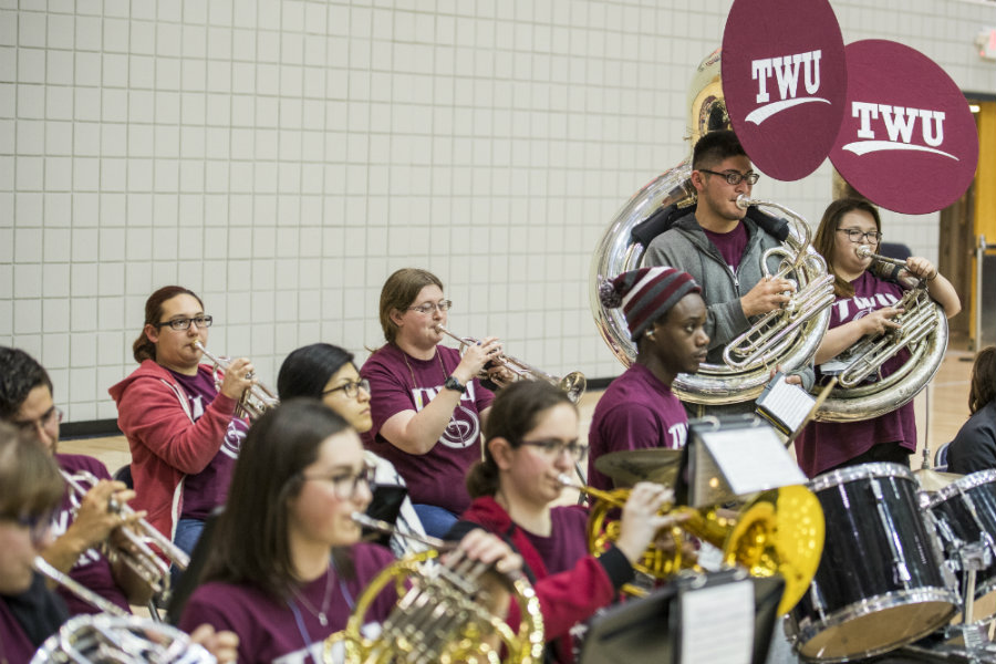 TWU students forming a band and playing instruments in Pioneer Hall during a basketball game.
