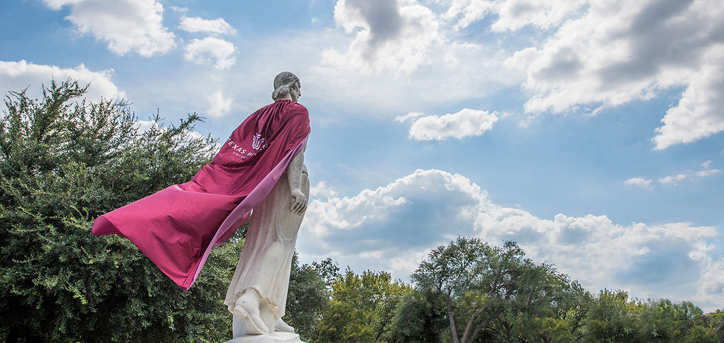 The Pioneer Woman statue on the Denton campus wearing a long cape with the TWU logo on it
