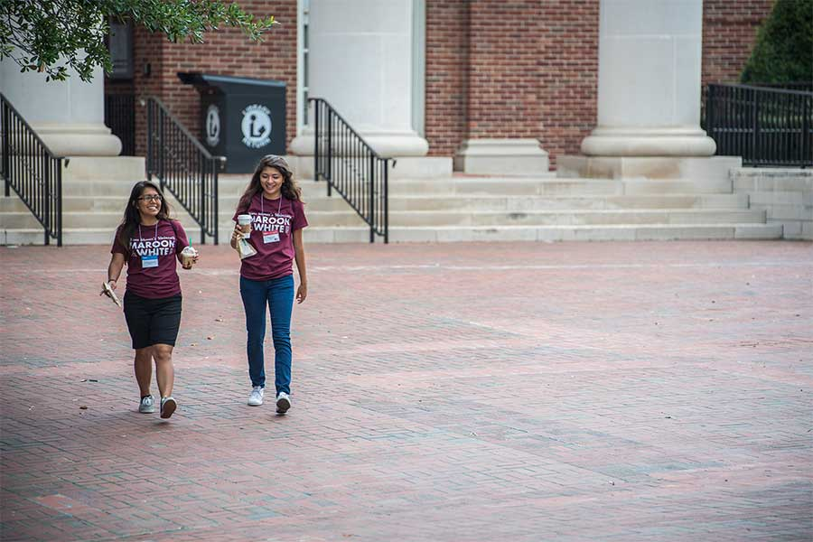 Two TWU students leave the library on the Denton campus.