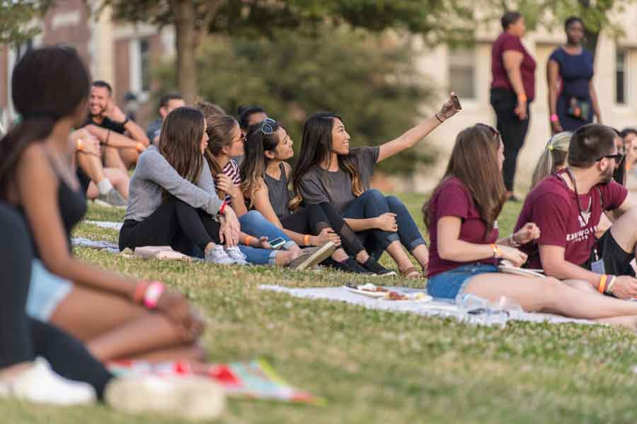A group of TWU students relax on the lawn during an on campus concert event.