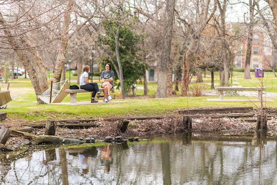 Two TWU students relax and sit on a bench outdoors on the Denton campus.