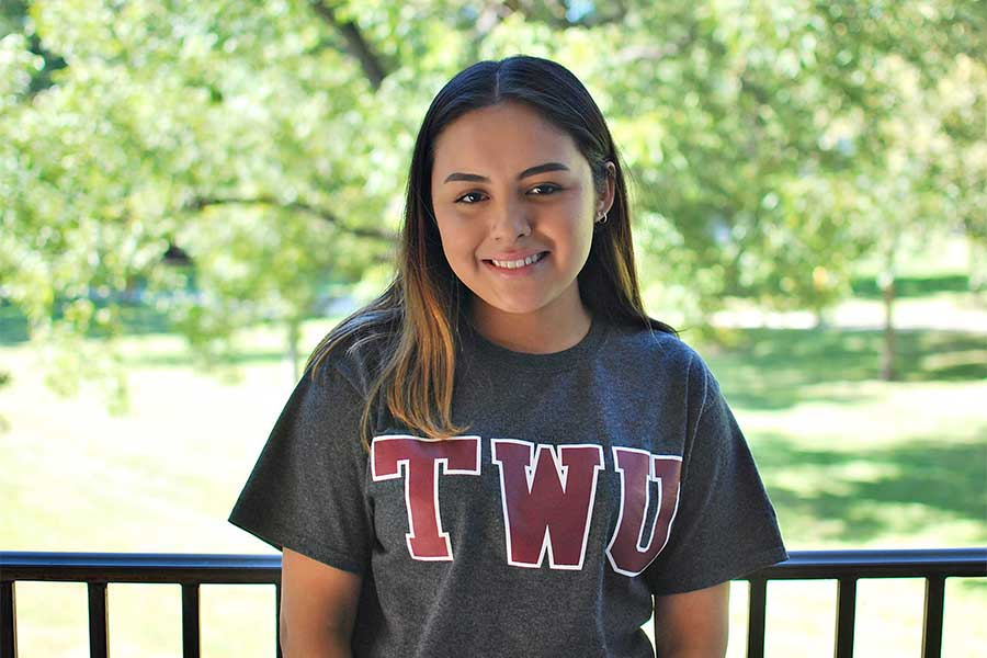 A TWU student smiles outdoors wearing a TWU shirt.