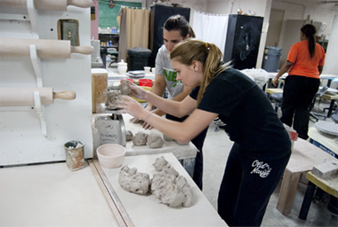 2 students working in a ceramics facility