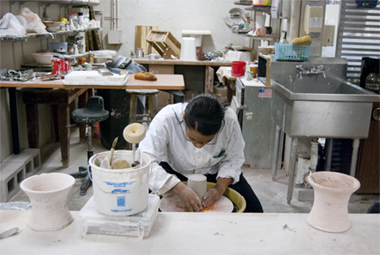 Student working at a pottery wheel