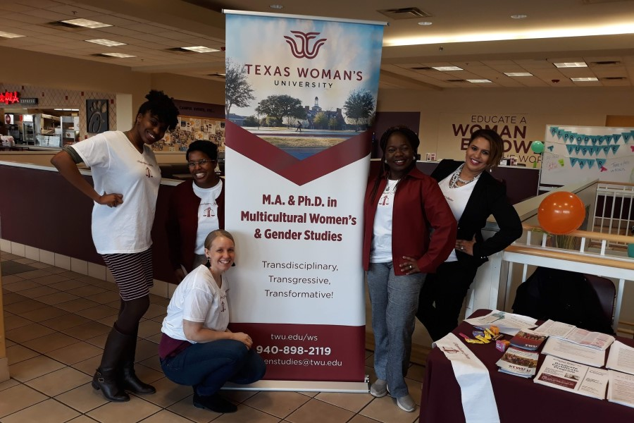 Planning committee members Foluso Oluade, Morgan May, Marcella Clinard, Esther Ajayi-Lowo, and Chelle Wilson, all MWGS graduate students, pose with their department's banner at the reproductive justice fair.