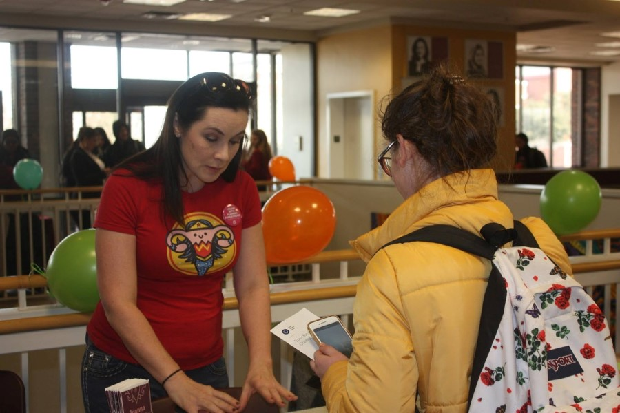 A local midwife discusses reproductive health with a TWU student at the reproductive justice fair.