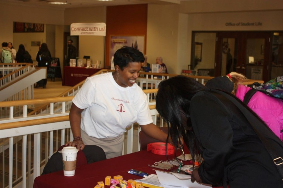 Morgan May, MWGS doctoral student and planning committee member, helps students sign in and enter a door prize drawing at the reproductive justice fair.