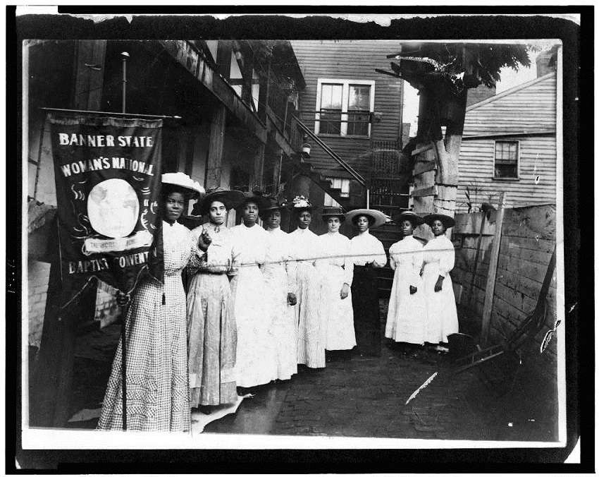 Nine African-American women posed, standing, full length, with Nannie Burroughs holding banner reading,