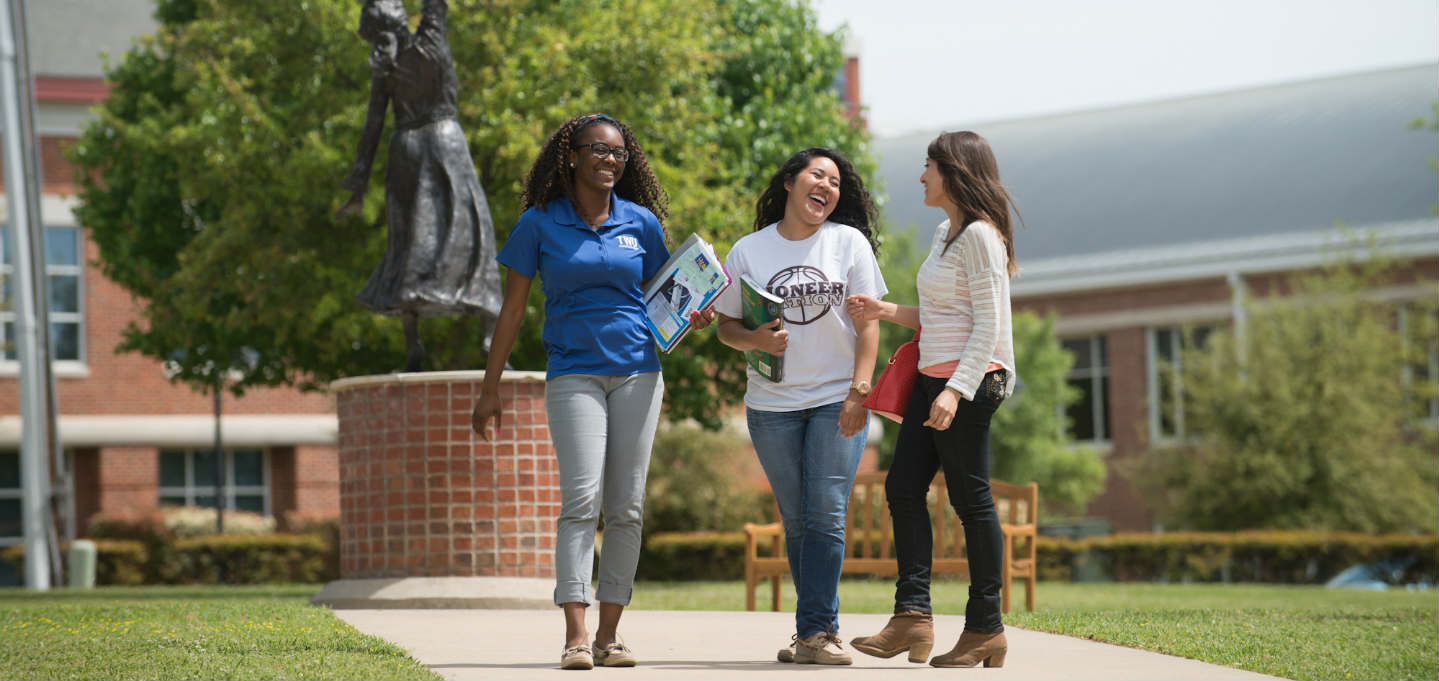 Three female student standing in front of the sculpture